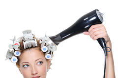 Female with hairdryer drying hairs in hair-curled Stock Photos