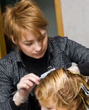 Female Hairstylist. A female hairstylist working on the hairstyle of a woman Stock Photo