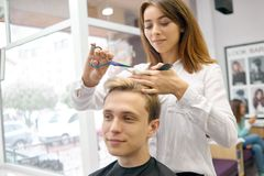 Female hairstylist doing haircut for handsome model with toned hair. royalty free stock image