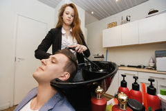 Female hairstylist washing male customer's hair in shop Royalty Free Stock Photos
