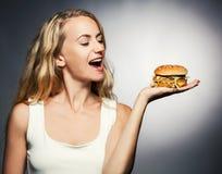 Female with hamburger. Woman eating unhealthy food royalty free stock image