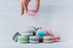 Female hand adds macaroons in a pile of almond cookies on a white wooden background, copy space. Female hand adds macaroons in a pile of almond cookies on a Royalty Free Stock Photos