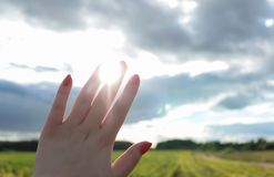 Female hand against a background of bright sun rays, blue sky, green field and landscape close-up Stock Photo