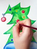 The female hand of the artist began to draw a green New Year tree with red balls in watercolors. Female hand of the artist draws a watercolor green New Year stock photography