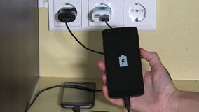 Female hand attach smart phone to wall charger and hold