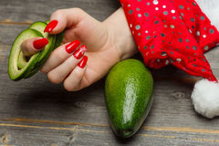 The female hand with beautiful festive New Year`s manicure holds the avocado fruit cut by rings. In style a rustic stock photos