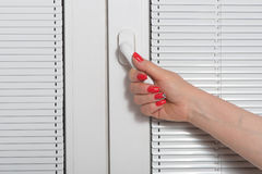 Female hand and blinds at window Royalty Free Stock Images