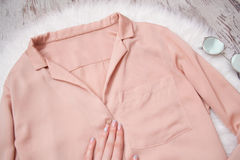 Female hand on the blouse pale pink glasses. Fashionable concept, top view.  Royalty Free Stock Photos