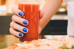 Female hand with blue manicure holding a glass of tomato juice i Stock Image