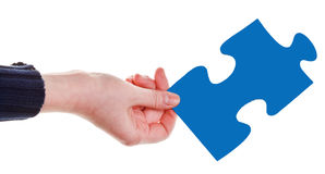 Female hand with blue puzzle piece Stock Images