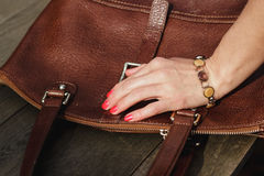 Female hand with bracelet holds a brown leather bag Royalty Free Stock Photo