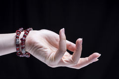 Female Hand Bracelets. Female hand, isolated on black background, is wearing some ornaments Royalty Free Stock Photo