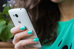 Female hand with bright manicure holding a mobile phone. Female hand with bright manicure holding a cell phone. in the picture prevails green, the model's face Stock Image