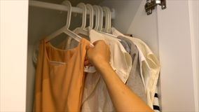 The hand of the woman is bringing the lady cloth hanging in the. Female hand is bringing cloths and fashion dress of female hanging in the wooden closet Stock Images