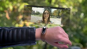 Female hand call girl friend who appears in hologram. Clock futuristic and technological. Park in background. stock footage