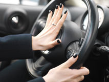 Female Hand On Car Horn. Manicured female fingers on a car horn, closeup with shallow depth of field stock images