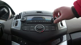 Female hand on the car radio tunes to radio and the radio searches for the display