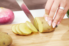 Female hand chopping potatoe Stock Photos