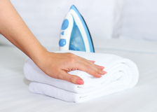 Female hand with a clean towel on the bed Stock Photography