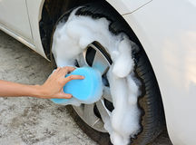Female hand is cleaning car tire with blue sponge Royalty Free Stock Photos