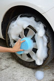 Female hand is cleaning car tire with blue sponge Stock Photos