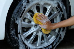 Female hand is cleaning car tire with sponge Royalty Free Stock Image