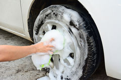 Female hand is cleaning car tire Royalty Free Stock Photography