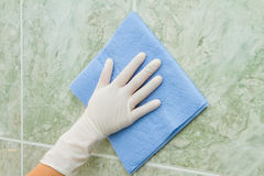 Female hand cleaning kitchen tiles with sponge Royalty Free Stock Photography