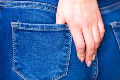 Female hand climbs into the pocket of jeans on the ass.  stock photos
