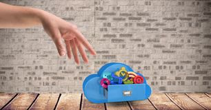Female hand with cloud shape and icons against brick wall. Digital composition of female hand with cloud shape and icons against brick wall Stock Image