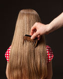 Female hand combing beautiful long hair Royalty Free Stock Images