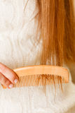 Female hand combing long hair. Royalty Free Stock Photo