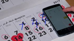 Female hand compare smart phone android calendar with paper calendar. VILNIUS, LITHUANIA - NOVEMBER 30, 2016: Female hand compare smart phone android calendar stock footage