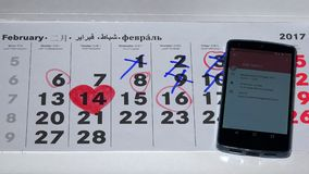Female hand compare smart phone and paper calendar events. VILNIUS, LITHUANIA - NOVEMBER 30, 2016: Female hand compare smart phone and paper calendar events stock video footage