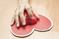 Female hand with computer mouse on table.valentine day Royalty Free Stock Image