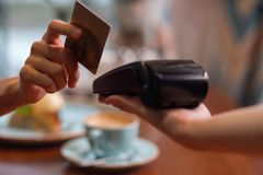 Female hand with credit card swipe through terminal. Credit card usage. Moment of payment with a credit card hold by female hand through terminal which carried Stock Photos