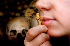 Female hand with cross on skulls and bones background. Female hand with wooden cross on skulls and bones background - religion concept stock image