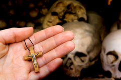 Female hand with cross on skulls and bones background. Female hand with wooden cross on skulls and bones background - religion concept stock images