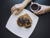 Female hand with a Cup of coffee and a beautiful chocolate cake stock image