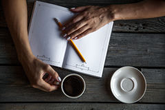 Female hand with a cup of coffee, taking notes. It works records. Business Stock Images