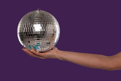 Female hand cupping a silver disco ball Stock Photo