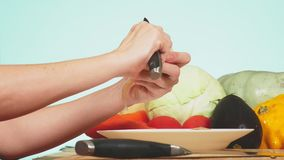 A female hand is cut with a knife an onion. mixture of vegetables for cooking vegetable stew. background color. 4k, the. Concept of healthy eating and stock footage