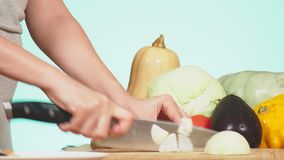 A female hand is cut with a knife an onion. mixture of vegetables for cooking vegetable stew. background color. 4k, the. Concept of healthy eating and stock video