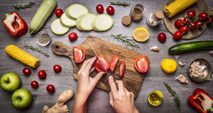 Female hand cut tomatoes on rustic grey background, around lie variety ingredients, vegetables, fruits, and spices, vegetarian foo Stock Images