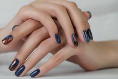 The female hand with dark blue glittered nails. Hand of the girl. Female manicure. Nail art manicure stock images