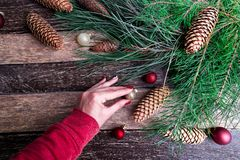 Female hand decorate Christmas or new year composition. Flat Lay.  Royalty Free Stock Image