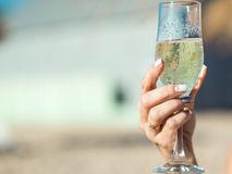 Female hand with delicious manicure holding a glass of sparkling wine on the sun. Vague background. Copy-space. Outdoor shot. Close up Royalty Free Stock Images