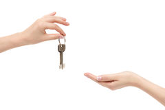 Female hand delivers keys to other hand on white background. Stock Images