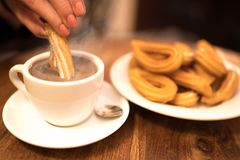 Female hand dipping churro into hot chocolate. Female hand dipping churro into steaming hot chocolate royalty free stock photo