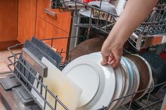 Female hand and dirty plates in dishwasher. Housework concept Stock Photos